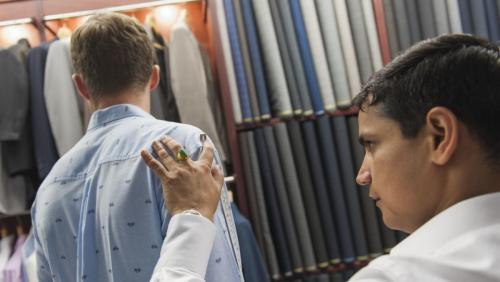 [4] Our tailor proceeds to take precise measurements of the shoulder – arm length